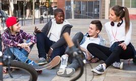 Adolescencias que charlan cerca de las bicis Fotos de archivo libres de regalías
