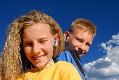 Adolescencias que escuchan la música Imagen de archivo libre de regalías