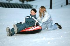 Adolescencias que juegan en la nieve Foto de archivo libre de regalías