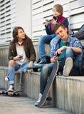 Adolescencias que juegan en smarthphones y que escuchan la música Fotografía de archivo