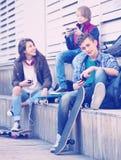 Adolescencias que juegan en smarthphones y que escuchan la música Fotografía de archivo libre de regalías