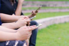 Adolescencias que mecanografían en los teléfonos móviles Fotos de archivo