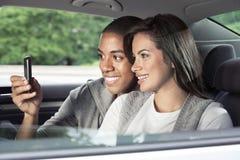 Adolescencias que miran smartphone en coche Fotos de archivo libres de regalías