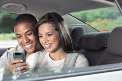 Adolescencias que miran smartphone en coche Foto de archivo