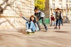 Adolescencias que montan rápidamente en rollerblades y el monopatín Imágenes de archivo libres de regalías