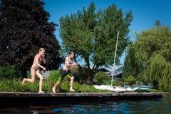 Adolescencias que saltan en el lago Fotos de archivo