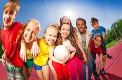 Adolescencias que se colocan en abrazo en la corte del partido de balonvolea Imagenes de archivo