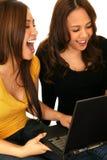 Adolescencias que se divierten con Internet Foto de archivo