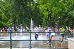 Adolescencias que se divierten en una fuente del parque Imagen de archivo libre de regalías