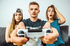 Adolescencias que se divierten que juega al videojuego Foto de archivo libre de regalías