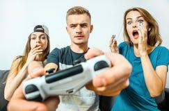 Adolescencias que se divierten que juega al videojuego Fotografía de archivo libre de regalías