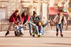 Adolescencias que se divierten rollerblading y que anda en monopatín Imágenes de archivo libres de regalías