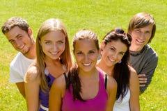 Adolescencias que se relajan en los amigos del parque felices Fotografía de archivo