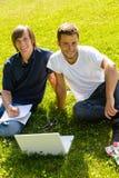 Adolescencias que se sientan en parque con los estudiantes de la computadora portátil Imagenes de archivo