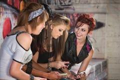 Adolescencias sonrientes con los teléfonos Fotos de archivo