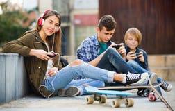 Adolescencias sonrientes felices que juegan en smarthphones Foto de archivo libre de regalías