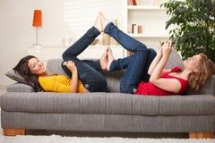 Adolescencias sonrientes que mienten en el sofá Fotos de archivo libres de regalías