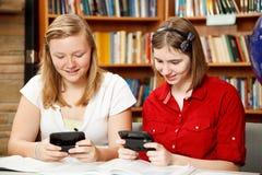 Adolescencias Texting en biblioteca Imagen de archivo libre de regalías