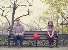 Adolescencias tristes que se sientan en el banco en el parque Foto de archivo