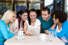 Adolescencias usando su tableta digital en un café Fotos de archivo libres de regalías