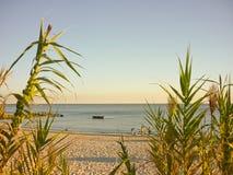 Adolescencias y un barco solo en la playa Fotos de archivo