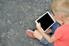 Adolescent à l'aide d'un comprimé numérique dans la rue photo stock