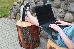 Adolescent à l'aide de l'ordinateur portable dehors image stock