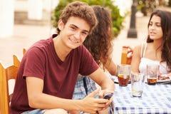 Adolescent à l'aide du téléphone portable se reposant au ½ de ¿ de Cafï avec des amis Photos stock