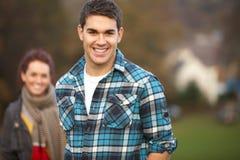 Adolescent à l'extérieur avec l'amie à l'arrière-plan Photographie stock