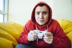 Adolescent émotif jouant la console de matchs à domicile utilisant un gamepad Jeux vidéo dans son temps disponible Regard dans l' Photo libre de droits