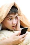 Adolescent étonné avec le téléphone portable image stock