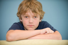 Adolescent. Young blond boy serious looking at the camera Royalty Free Stock Image