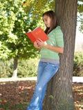 Adolescent affichant un livre images stock
