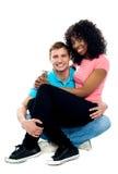 Adolescent africain s'asseyant sur les genoux d'amis Photo stock