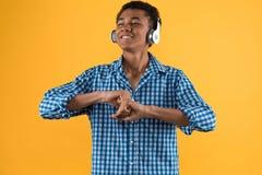 Adolescent afro-américain heureux dans la danse d'écouteurs image stock