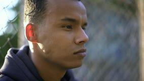 Adolescent afro-américain regardant pensivement en avant, préoccupé par l'avenir image libre de droits