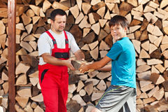 Adolescent aidant le père à empiler le bois de chauffage photos libres de droits