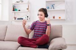 Adolescent appréciant la musique dans des écouteurs à la maison Images stock