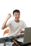 Adolescent asiatique à l'aide de l'ordinateur avec le geste de victoire Photo libre de droits