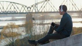 Adolescent asiatique de brune de métis écoutant la musique avec ses écouteurs banque de vidéos