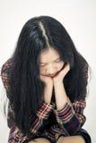 Adolescent asiatique triste avec la tête dans des mains Images stock