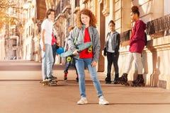 Adolescent aux cheveux bouclés heureux tenant la planche à roulettes Image libre de droits