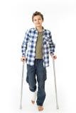 Adolescent avec des béquilles et un bandage sur sa bonne jambe Photographie stock