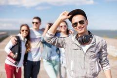 Adolescent avec des lunettes de soleil et des amis dehors Photos stock