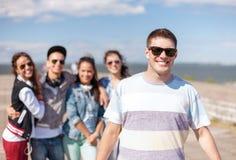 Adolescent avec des lunettes de soleil et des amis dehors Images stock