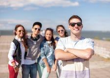 Adolescent avec des lunettes de soleil et des amis dehors Image stock