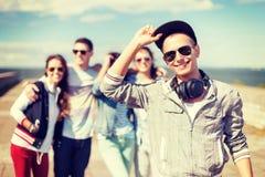 Adolescent avec des lunettes de soleil et des amis dehors Photo libre de droits