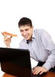 Adolescent avec l'ordinateur portable et la pizza photographie stock