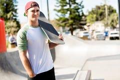 Adolescent avec la planche à roulettes se tenant dehors Photos stock