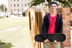 Adolescent avec la planche à roulettes se tenant dehors Photo stock